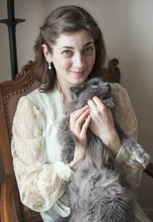 gato gris: Retrato de una mujer joven en un vestido vintage que sostiene su gato gris.