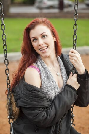 auburn hair: Beautiful young woman with red hair on a swing.