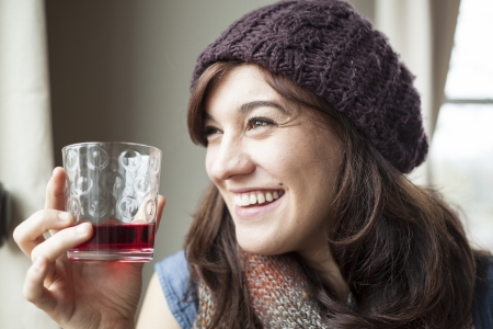 cranberry: Beautiful young woman drinking glass of cranberry juice