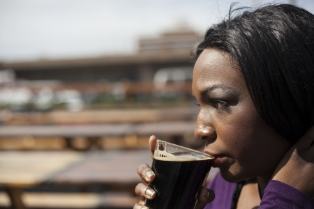 stout: Young African American woman drink stout from a pint glass. Stock Photo