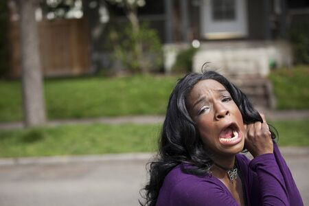 american content: Horrified young African American woman in a purple top.