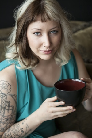 Portrait of a beautiful young woman with brown and blond hair looking right into the camera. She is also holding a black coffee cup and wearing a blue dress. photo