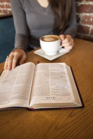 Portrait of a young woman with a white coffee cup reading the book of Mark in the Bible Stock Photo