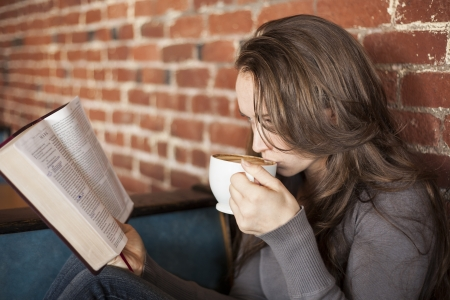 christian women: Portrait of a young woman with a white coffee cup reading the book of Mark in the Bible Stock Photo