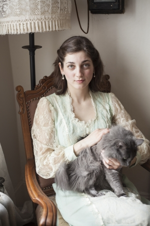 Portrait of a beautiful young woman looking directly at the camera. She is in a vintage dress and sitting in an antique chair holding her gray cat.