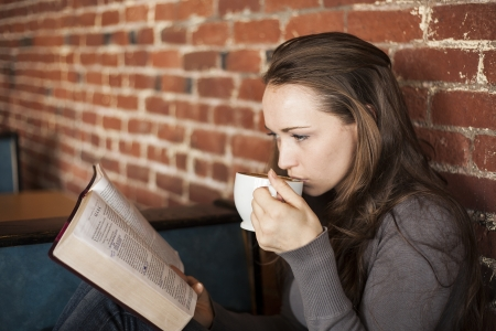 holy bibles: Portrait of a young woman with a white coffee cup reading the book of Mark in the Bible Stock Photo