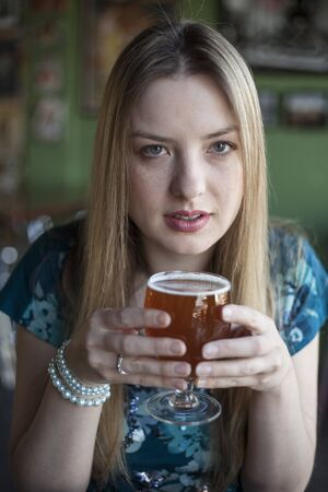 causcasian: Portrait of a blonde woman with blue eyes drinking a goblet of beer.