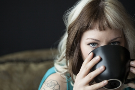 Portrait of a beautiful young woman with brown and blond hair holding a black coffee cup and wearing a blue dress. photo