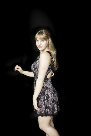 causcasian: Portrait of a beautiful blond woman in a pretty dress on a black background.
