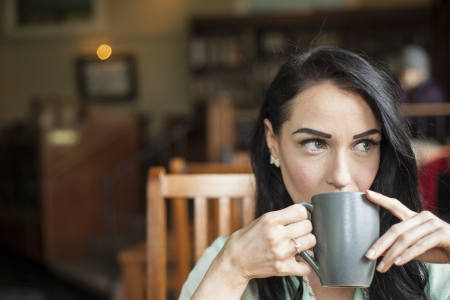 Beautiful young woman with dark brown hair and eyes holding a gray coffee cup. Stock Photo
