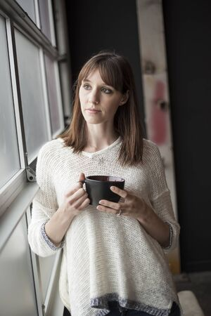 dark brown hair: Beautiful young woman with dark brown hair and eyes with a black coffee cup.