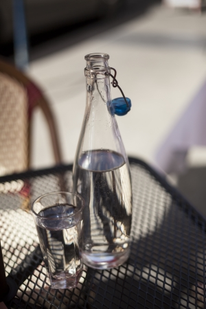 carafe: Carafe and glass filled with water sitting on a metal cafe table on a sunny day.