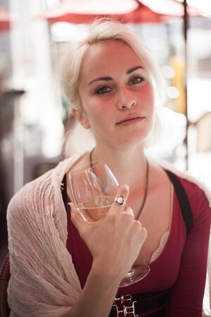 soulful eyes: Portrait of a beautiful blond woman shot outdoors at a cafe. She has green eyes and bleached blond hair and is holding a glass of white wine. Stock Photo