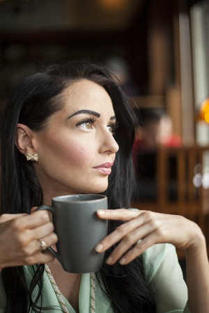dark brown hair: Beautiful young woman with dark brown hair and eyes holding a gray coffee cup. Stock Photo