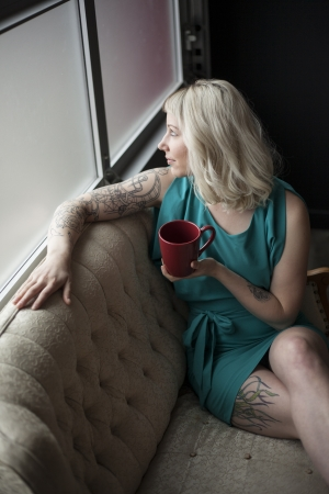 Portrait of a beautiful young woman with brown and blond hair. She is also holding a red coffee cup and wearing a blue dress. photo