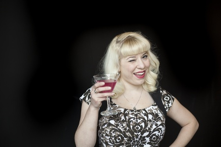 Portrait of a beautiful young woman with blond hair drinking a pink martini. photo