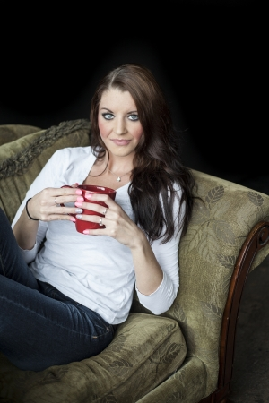 black hair blue eyes: Portrait of a beautiful young woman with brown hair and blue eyes. She is sitting in a green chair and drinking coffee from a red cup.
