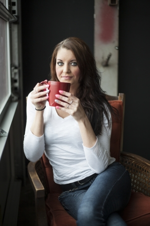 Portrait of a beautiful young woman with brown hair and blue eyes. She is sitting in an orange chair and drinking coffee from a red cup. Stock Photo