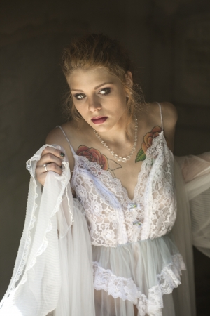 crypt: Portrait of a beautiful young woman in white lingerie walking out of a crypt.