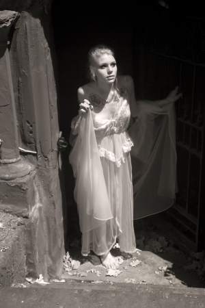 crypt: Infrared portrait of a beautiful young woman in white lingerie walking out of a crypt.