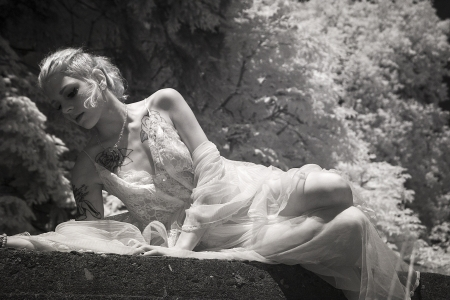 crypt: Infrared portrait of a beautiful young woman in white lingerie lying on top of a crypt. Stock Photo