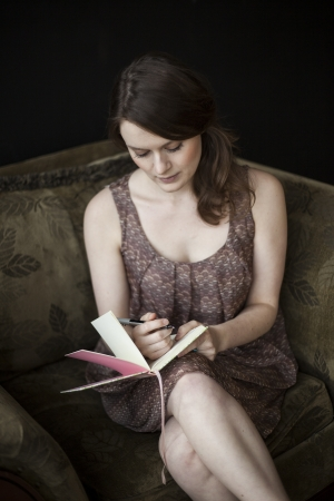 journals: Portrait of a beautiful young woman in a dress writing in her journal