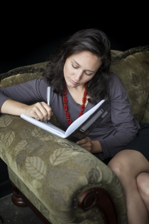 Portrait of a beautiful young woman seated and writing in her journal.