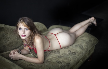 panties: Portrait of a beautiful young woman in her underwear lying on a couch.