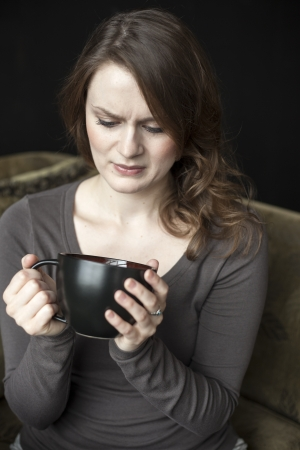 unsatisfied: Portrait of a beautiful young woman with beautiful green eyes and brown hair making an ugly facial expression while she holds a black coffee cup. Stock Photo