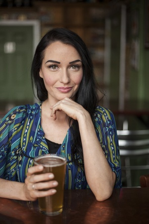 pilsner beer: Beautiful young woman with dark brown hair and eyes and a very cute smile and a pint of beer.