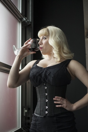 Portrait of a beautiful young woman with blond hair drinkiing a glass of wine. photo