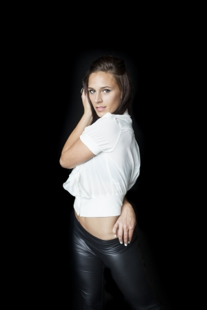 black pants: Beautiful young woman with brown hair and eyes in a white top and black leather pants.