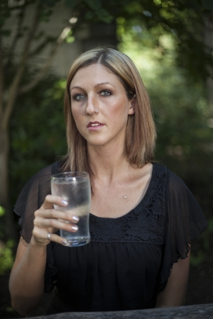 causcasian: Portrait of a blonde woman with blue eyes outdoors with a glass of water. Stock Photo