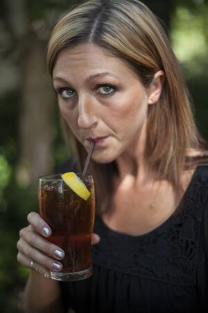 Portrait of a blonde woman with blue eyes outdoors and glass of iced tea with lemon.