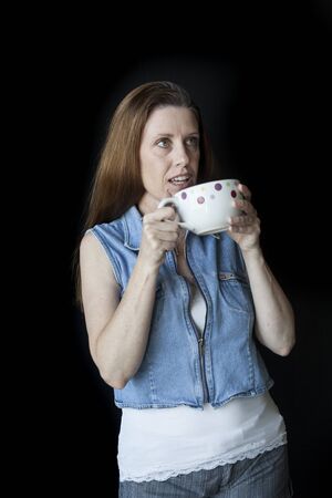 causcasian: Portrait of a beautiful woman with a nice smile and white polka dot coffee cup. Stock Photo