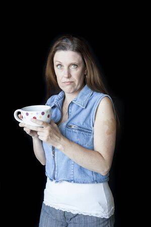 causcasian: Portrait of a beautiful woman with a strange facial expression and white polka dot coffee cup.