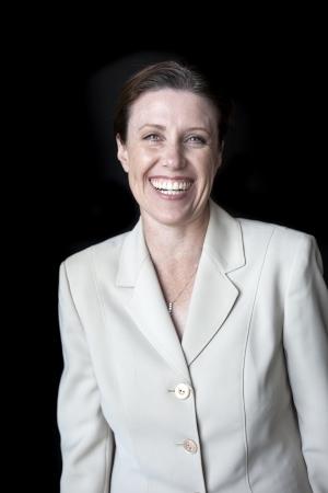 검은 배경에 총 비즈니스 정장에서 멋진 미소와 아름 다운 여자의 초상화.