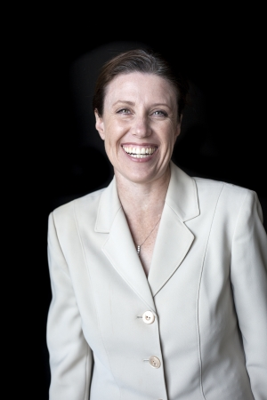 Portrait of a beautiful woman with a nice smile in a business suit shot on a black background. photo