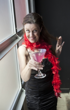 Portrait of a beautiful woman in a black dress with pink martini and red boa. photo