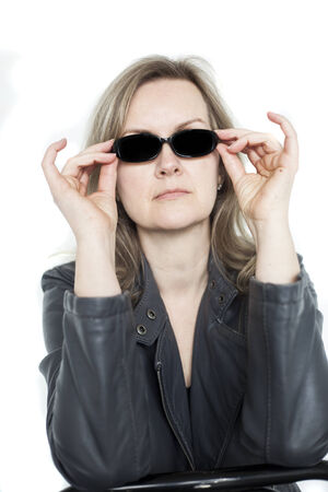 Portrait of a blonde woman on a white putting on her sunglasses. photo