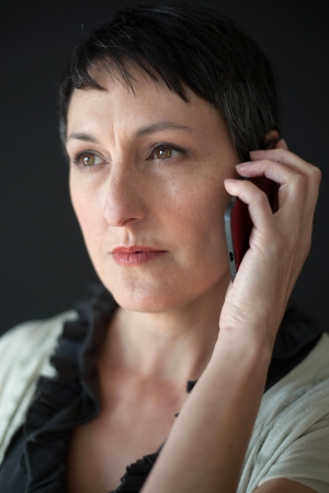 Beautiful older woman with short brown hair and eyes talking on a cell phone. photo