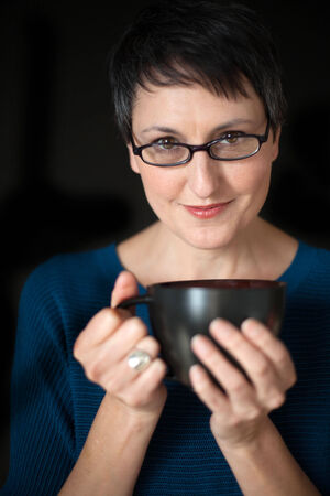 bookish: Beautiful older woman with short brown hair and eyes, glasses, and coffee cup on a black background.