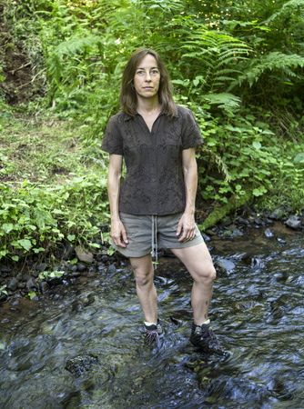 roughing: Portrait of a middle aged female hiker crossing a stream.