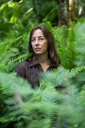 roughing: Portrait of a middle aged female hiker surrounded by ferns.