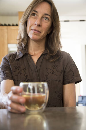 unwinding: Portrait of a middle aged woman in the kitchen drinking wine.