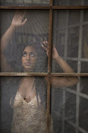 mujer golpeada: Mujer india joven hermosa en un camisón atractivo mirando por edad, puerta de pantalla maltratada.