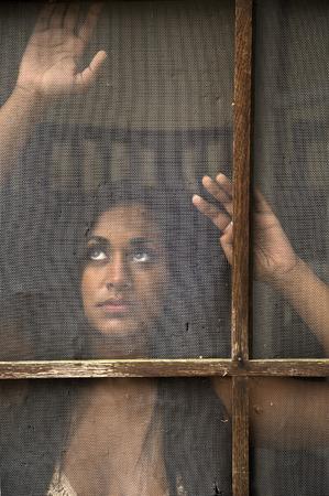 mujer golpeada: Joven india hermosa que mira hacia fuera viejo, puerta de pantalla maltratada.