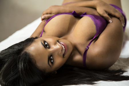 breast sexy: Beautiful, busty, young Indian woman in an attractive, silky purple negligee. Stock Photo
