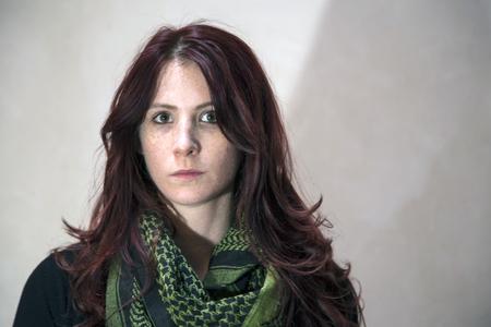 빨간 머리와 갈색 눈과 녹색 스카프와 아름 다운 젊은 여자의 초상화.