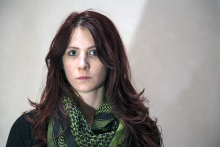 Portrait of a beautiful young woman with red hair and brown eyes and green scarf.